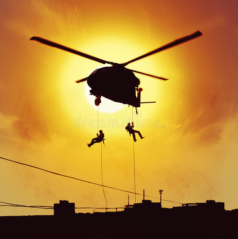 Helicopter assault special forces. Special forces operators are fastroping from helicopter royalty free stock images