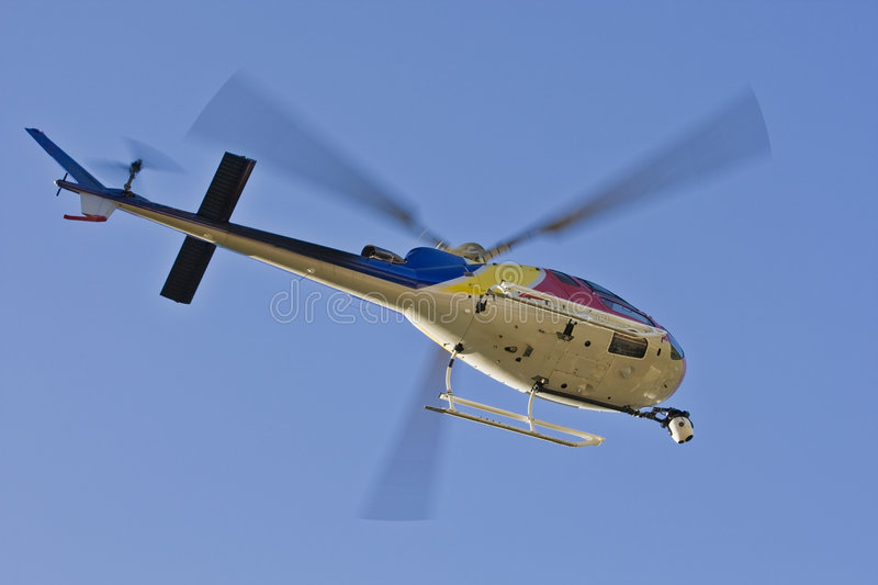 Helicopter with camera. A helicopter with a camera. A motion blur on rotor blades royalty free stock photography