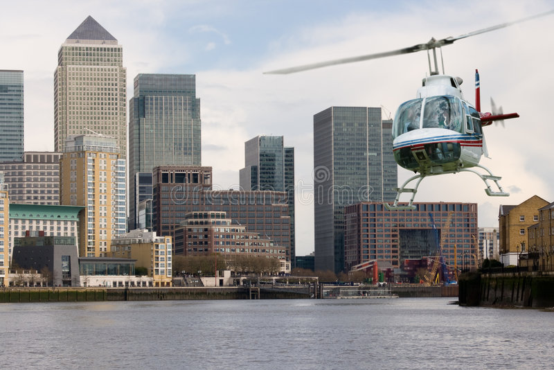 Helicopter Canary Wharf. Helicopter flying along the Thames with Canary Wharf background stock image