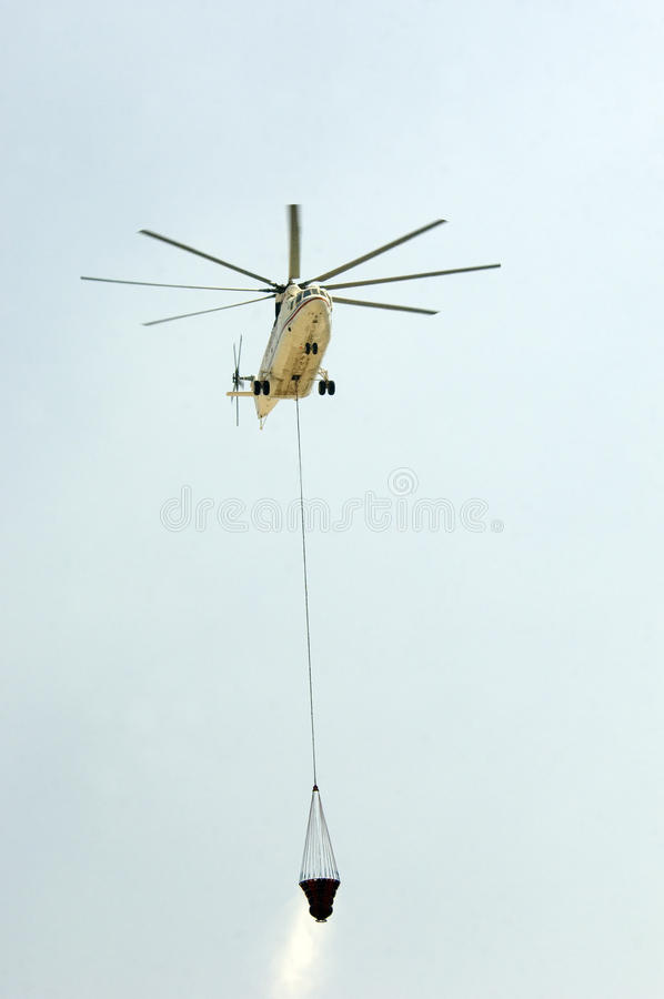Helicopter carrying water to fire stock photos