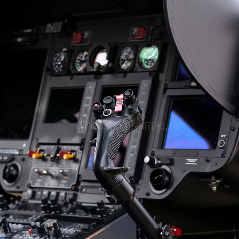 Cockpit of a helicopter. Helicopter cockpit from the side with lots of buttons and screens, the joystick in the front is in focus royalty free illustration