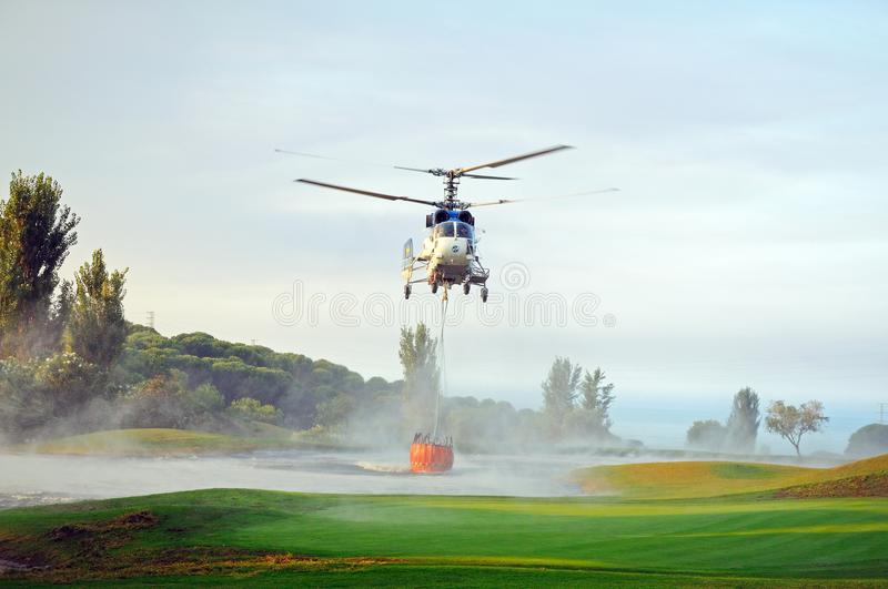 Helicopter collecting water for fire fighting, Spain. Kamov Ka-32A11BC helicopter (registration EC-JSQ) collecting water for fire fighting from a golf course royalty free stock image