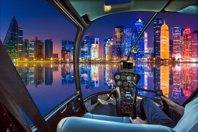 Helicopter on Doha Bay. Helicopter cockpit interior flying over Doha Bay harbour with scenic skyline reflecting at blue hour. Night scene waterfront in Doha sea royalty free stock photos