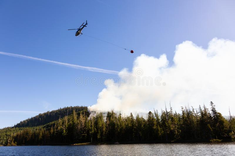 Helicopter Fighting Fires in BC. Helicopter fighting BC forest fires during a hot sunny summer day. Taken near Port Alice, Northern Vancouver Island, British stock image