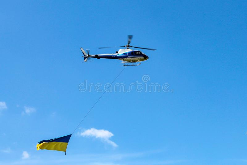 The helicopter flies with the national state yellow blue flag of Ukraine. Ukrainian flag in the sky over the city Dnepr royalty free stock photography