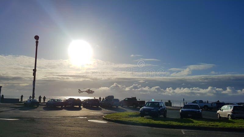 Helicopter flies overhead on beautiful Oregon Coast beach scene stock photo