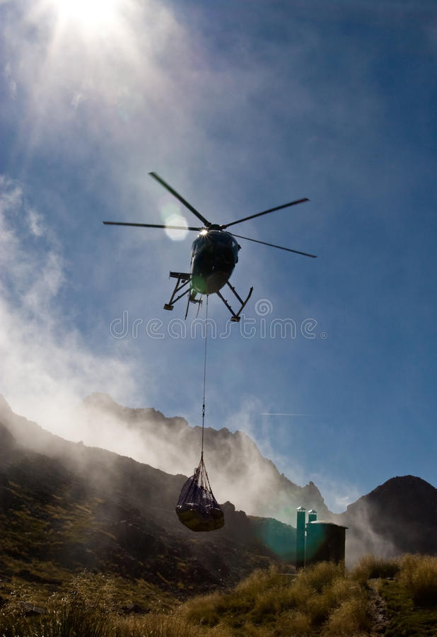 Helicopter flies in supplies to mountain hut royalty free stock photo