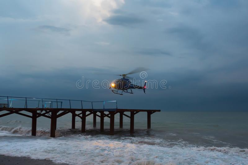 Helicopter, flies up during a marine gale. Air transport in bad weather conditions.  royalty free stock photos