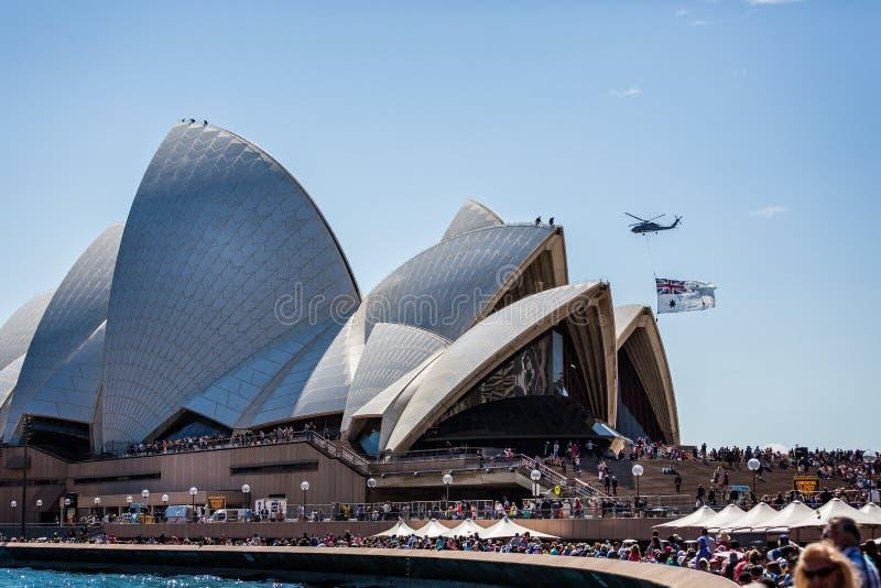 Helicopter flying Australian flag flying close to the Sydney Opera House in Sydney, Australia royalty free stock photo