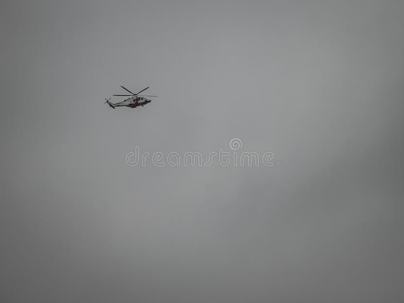 Helicopter flying in a grey sky stock image
