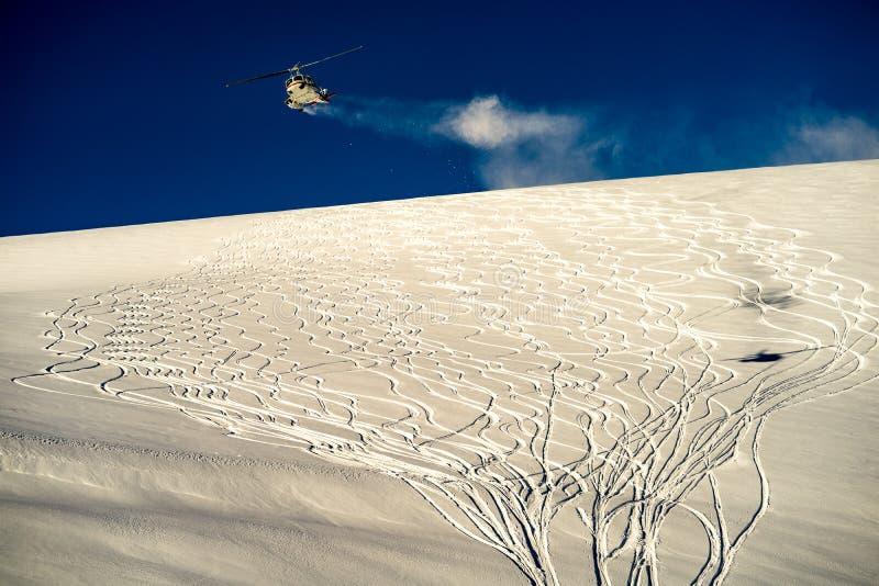 Helicopter flying over ski tracks stock photo