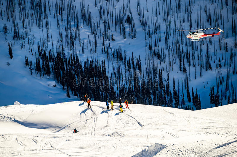 Helicopter flying over skiers royalty free stock images