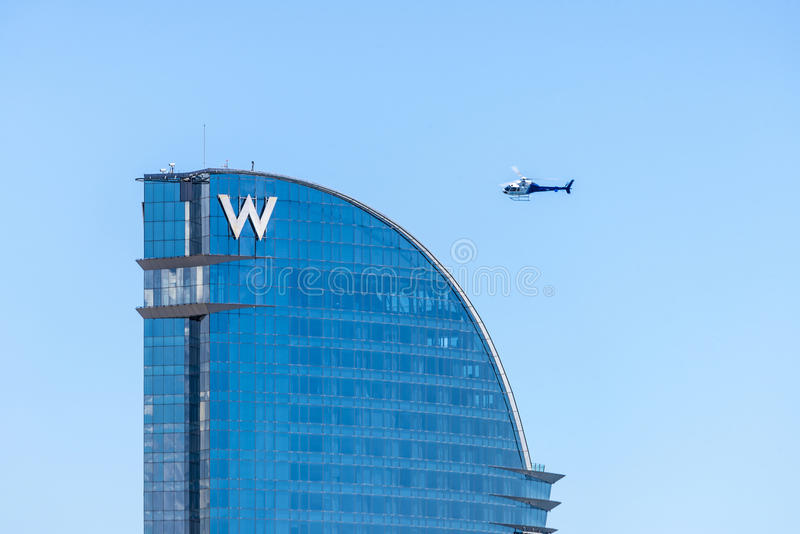 Helicopter flying over the W hotel in Barcelona. Barcelona, Spain - May 23, 2014: Helicopter flying over the W hotel, designed by Architect Ricardo Bofill, also royalty free stock image