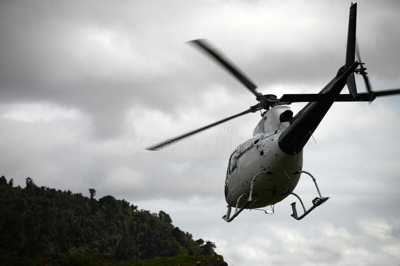 Helicopter heading off to the hills royalty free stock image
