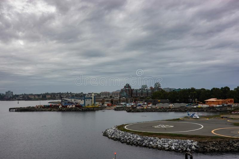 A helicopter on a helipad next to a cruise ship dock at the port in Victoria, Canada. Victoria/Canada-9/14/19: A helicopter on a helipad next to a cruise ship royalty free stock photography