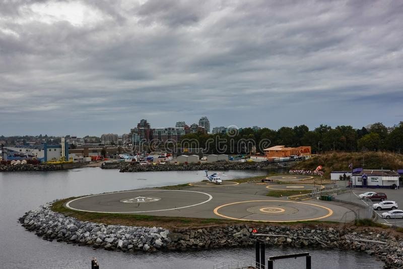 A helicopter on a helipad next to a cruise ship dock at the port in Victoria, Canada. Victoria/Canada-9/14/19: A helicopter on a helipad next to a cruise ship stock image