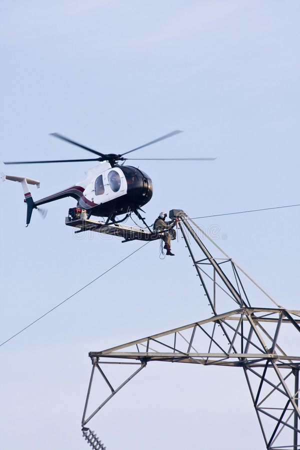 Helicopter High lines construct. Contractors are installing new high voltage transmission towers to carry electricity across the country, final work is done with royalty free stock images