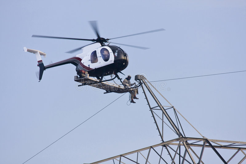 Helicopter High lines Repair. Contractors are installing new high voltage transmission towers to carry electricity across the country, final work is done with stock photos