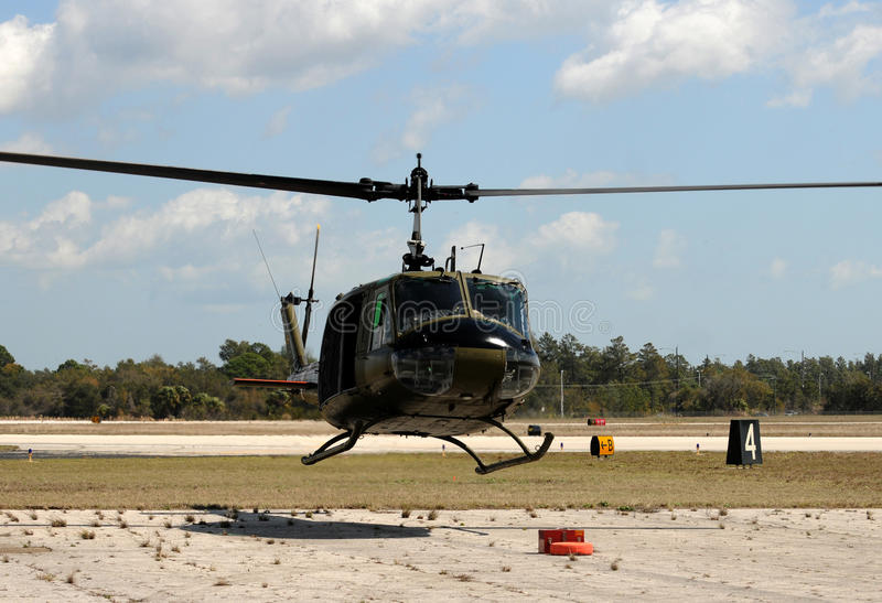 Helicopter hovering. Military helicopter in green color hovering above the ground royalty free stock photos