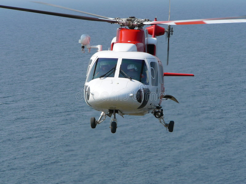 Helicopter hovering. A helicopter (Sikorsky S-76) hovering over sea (ocean) water royalty free stock images