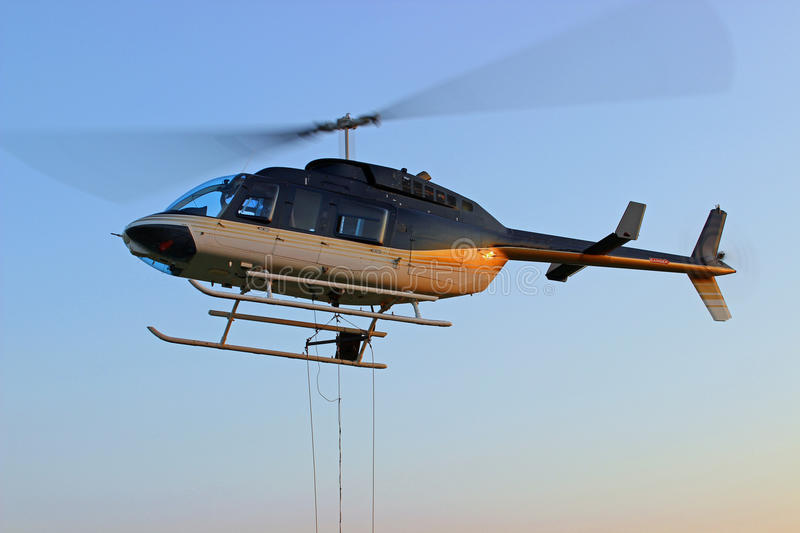 Helicopter. Hovering while seed hopper is loaded while cabled to it stock photo