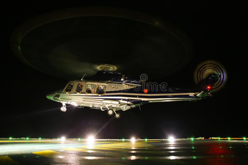 Helicopter landing in offshore oil and gas platform on deck or parking area. Helicopter night flight training of pilot.  royalty free stock photo