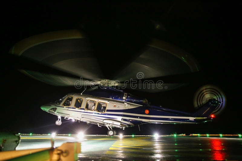 Helicopter landing in offshore oil and gas platform on deck or parking area. Helicopter night flight training of pilot.  royalty free stock photography