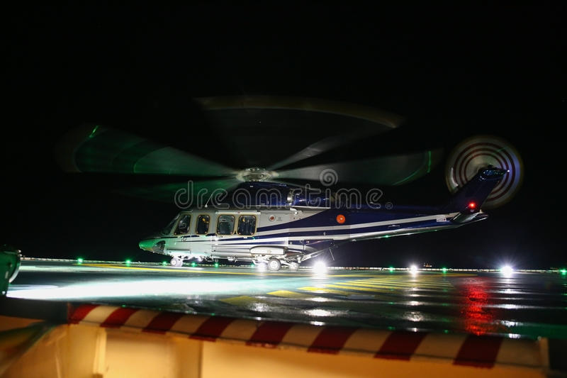 Helicopter landing in offshore oil and gas platform on deck or parking area. Helicopter night flight training of pilot.  stock photo