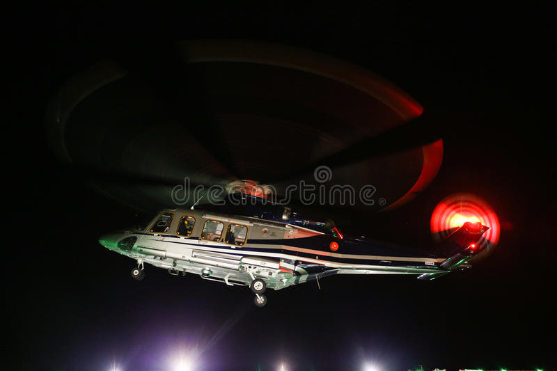 Helicopter landing in offshore oil and gas platform on deck or parking area. Helicopter night flight training of pilot stock images