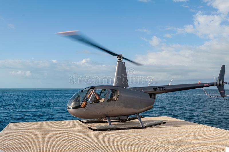 Helicopter landing at the pontoon helipad near Reef World on the Great Barrier Reef, Whitsunday Islands. Hook Reef, Whitsunday Island, Queensland, Australia stock image