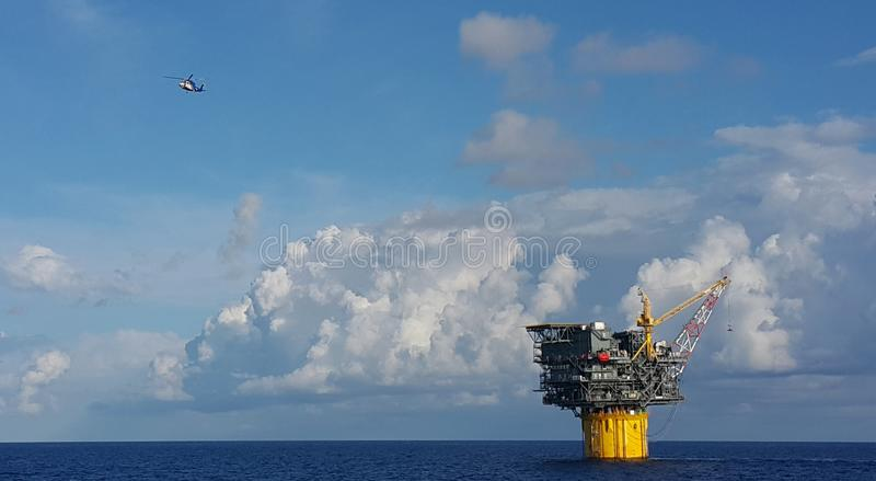 Crew change day. A helicopter leaving an oil and gas floating production and storage spar in Gulf Of Mexico royalty free stock images