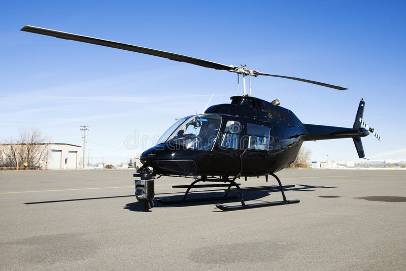 Helicopter parked at airport lot. Black helicopter with camera mounted on front parked at airport tarmac royalty free stock images