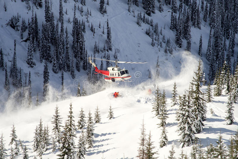 Helicopter picking up skiers stock photography