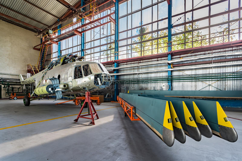 Helicopter repair stand in the hangar. Helicopter without blades in repair stand in the aviation hangar. Helicopter blades stand nearby stock photos