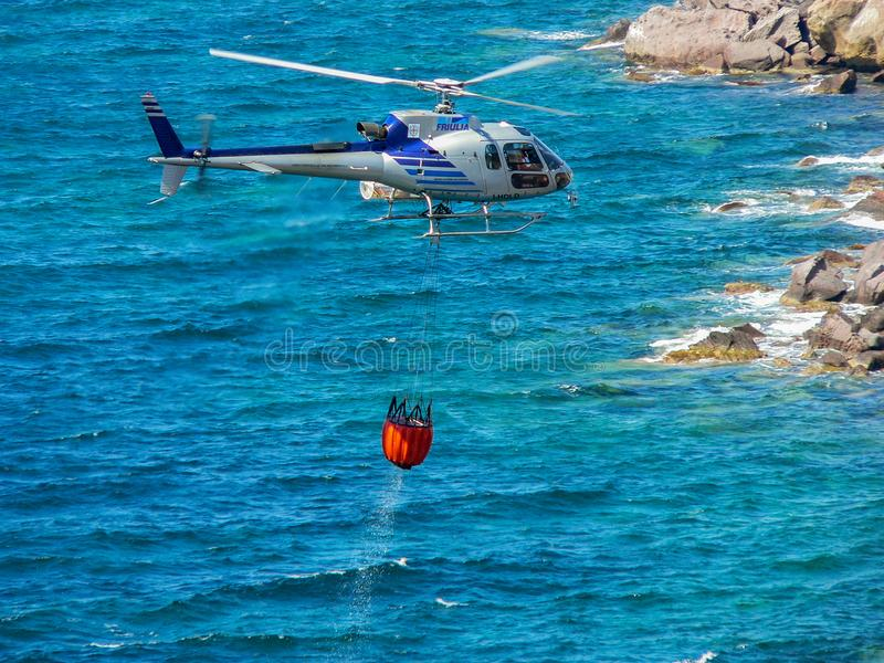 Safety. Rescue and fire fighting activities. Helicopters equipped with lots collects water from the sea to extinguish a fire on the ground royalty free stock photography