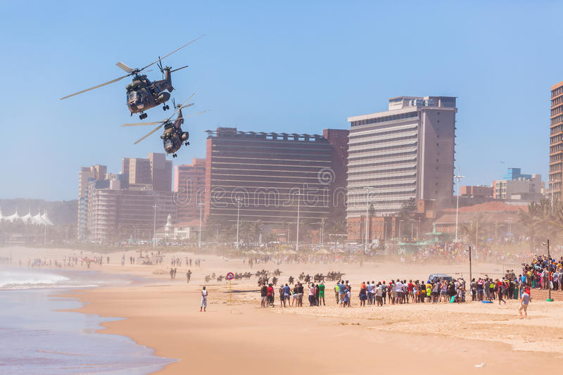 Helicopters Soldiers Beach Flying Public. Helicopters military aircrafts dropping soldiers training public event Durban beach`s summer day stock photography