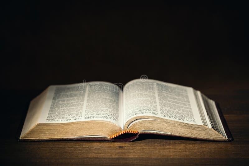 Helig bibel i mörkret på ett pastorskrivbord arkivfoto