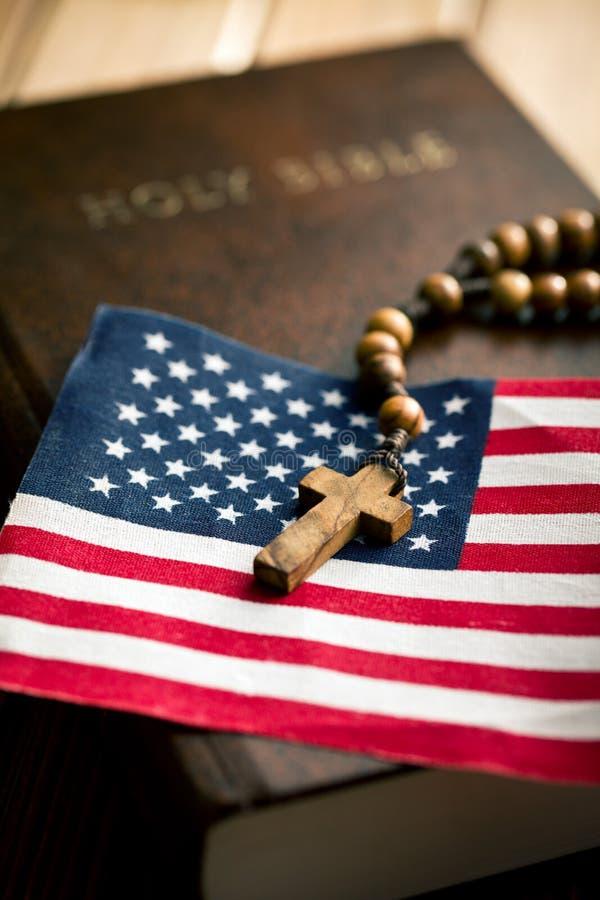 Helig bibel med amerikanska flaggan och korset arkivfoto