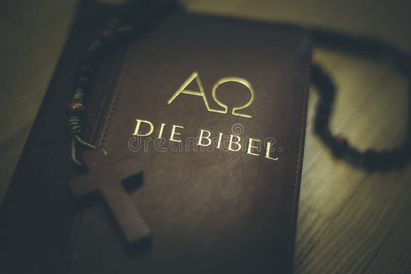 Helig bibel och radband: Kristen bibel och radband p? ett tr?skrivbord arkivbilder