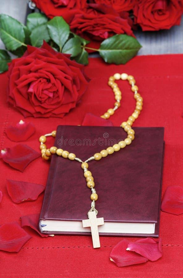 Helig bibel, radband och bedöva röda rosor royaltyfria foton