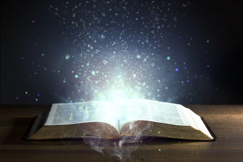 Helig bibel som är öppen med glödande ljus royaltyfri foto