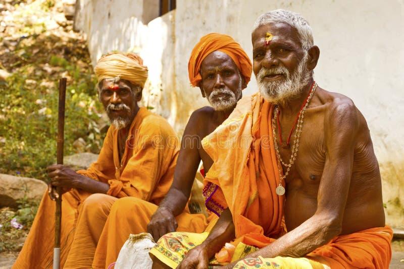 Heliga Sadhu män i saffran färgar klädvälsignelse i Shiva Temple. Januari 15, 2013 i Indien, Tamil Nadu, Tiruvanamalai royaltyfria bilder