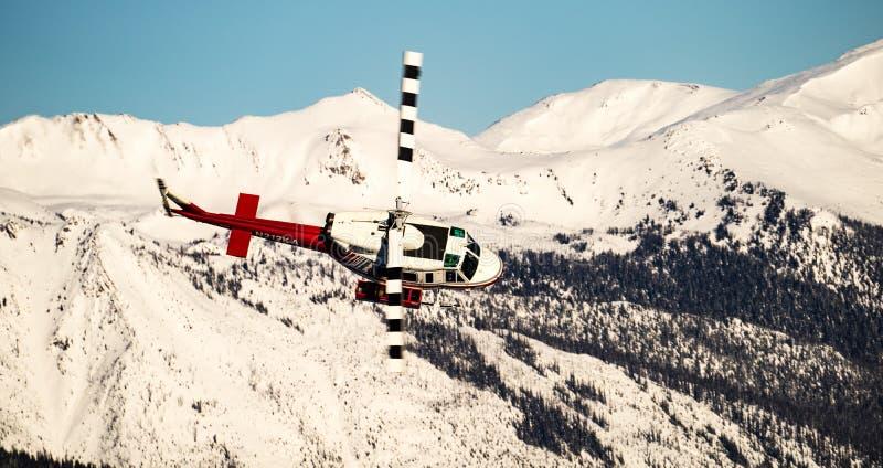 Helikopter deponujący pieniądze przed górami obraz royalty free