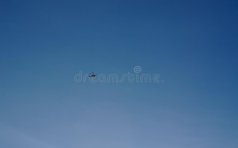 Helikopter die met blauwe hemelachtergrond vliegen stock foto