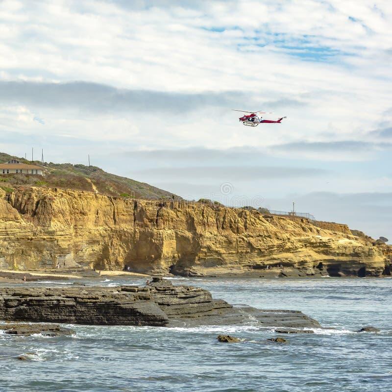 Helikopter die op bewolkte hemel over Zonsondergangklippen vliegen royalty-vrije stock afbeeldingen