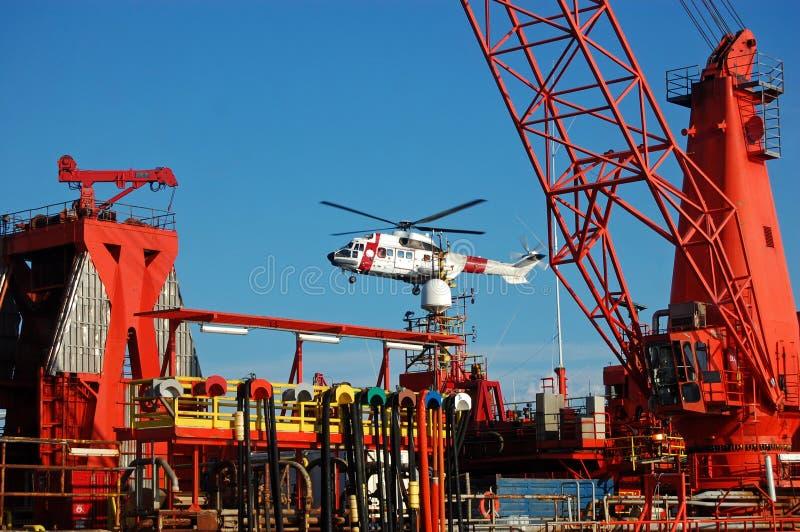 Helikopter die op een Semi submergible installatie landt. stock foto's