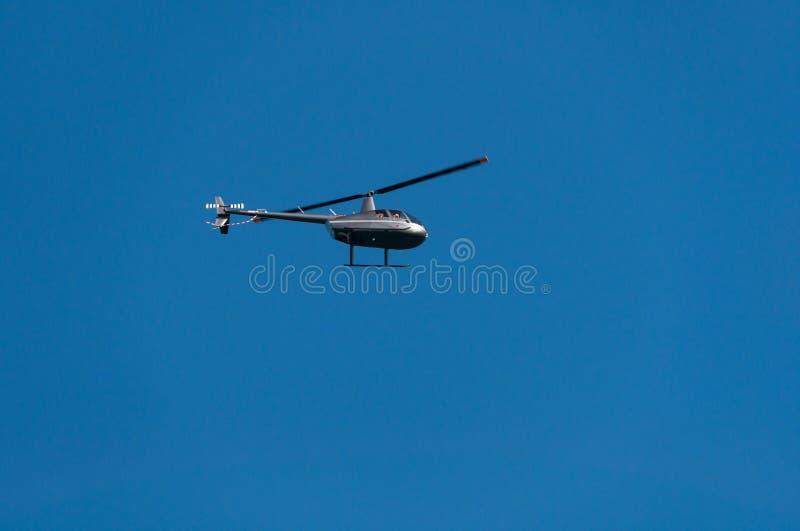 Helikopter die tegen duidelijke blauwe hemel op de achtergrond vliegen stock foto's