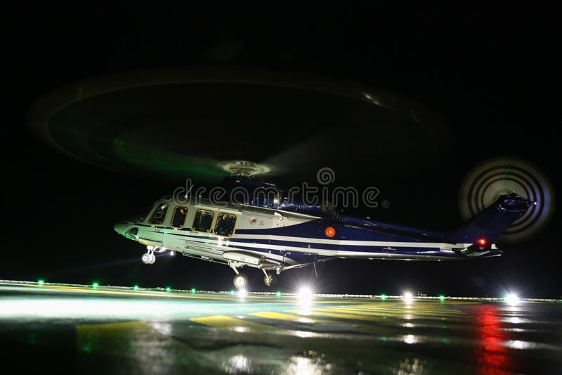 Helikopter die in zeeolie en gasplatform op dek of parkeerterrein landen De vlucht van de helikopternacht opleiding van proef stock afbeelding