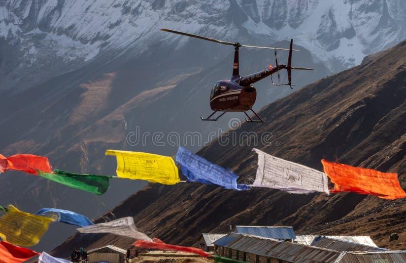 Helikopter en kleurrijke tibetan gebedvlaggen in Annapurna-Basiskamp, Himalayagebergte stock foto