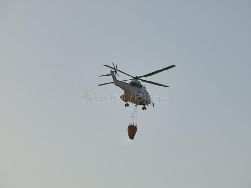 Helikopter för brandstridighet med vattenpåsen royaltyfria bilder